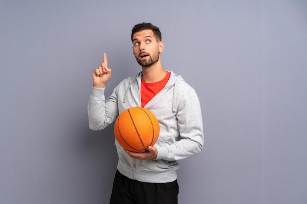 Il giovane uomo bello del giocatore di pallacanestro che intende realizzare la soluzione mentre solleva un dito su