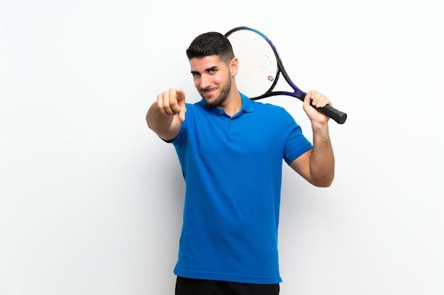 Il giovane uomo bello del tennis sopra la parete bianca indica il dito con un'espressione sicura