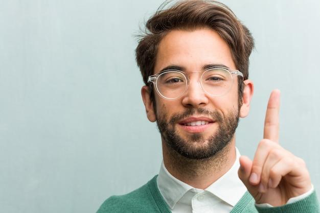 Il giovane uomo bello dell'imprenditore affronta il primo piano che mostra il numero uno, simbolo di conteggio