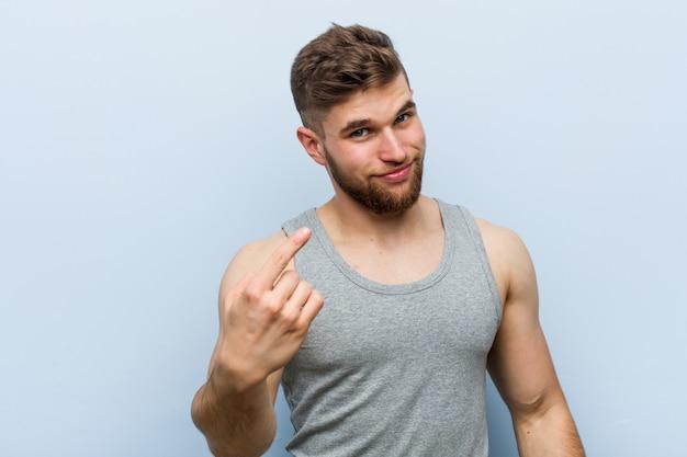 Il giovane uomo bello di forma fisica che indica con il dito voi come se invitare si avvicini.