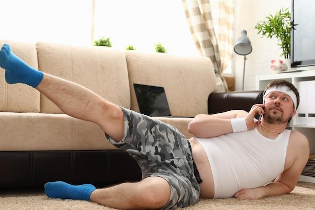 Il giovane uomo bello di forma fisica si trova sulla stuoia grassa con