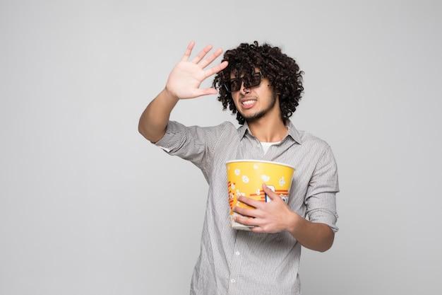 Il giovane uomo bello indossa i vetri 3d con capelli ricci che tengono una ciotola di popcorn sopra la parete bianca isolata