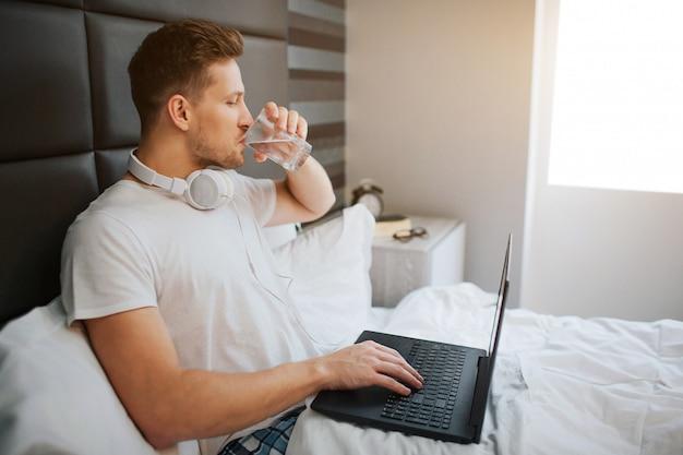 Il giovane uomo bello si siede a letto questa mattina. beva acqua. modello maschio tenere laptop. cuffie al collo.