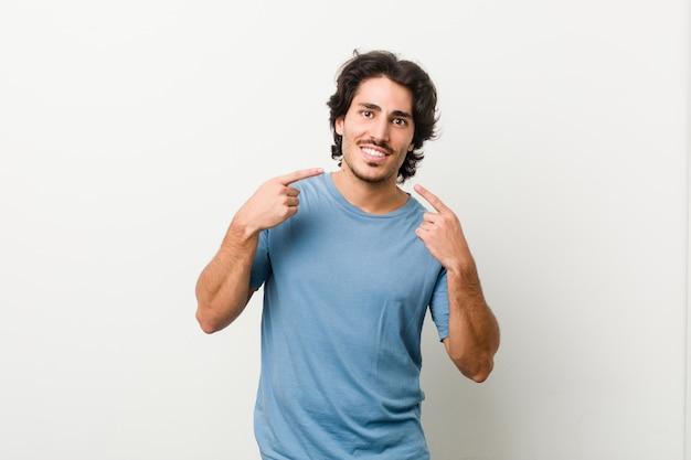Il giovane uomo bello sorride, indicando le dita a se stesso