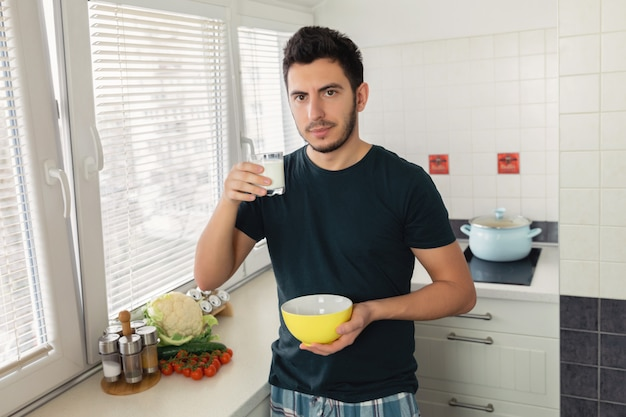 Il giovane uomo bello sta facendo colazione nella cucina di casa. il ragazzo si preparò la farina d'avena e un bicchiere di latte per colazione.