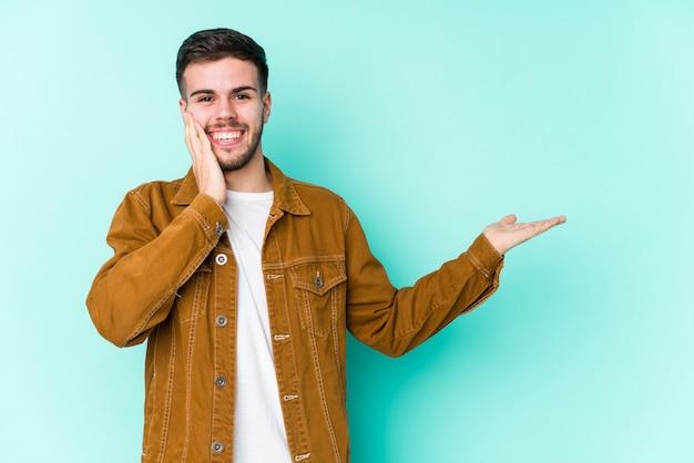 Il giovane uomo bello tiene lo spazio della copia su una palma, tiene la mano sulla guancia stupito e felice.