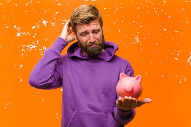 Il giovane uomo biondo con un porcellino salvadanaio che indossa una maglia con cappuccio viola ha danneggiato la parete arancio