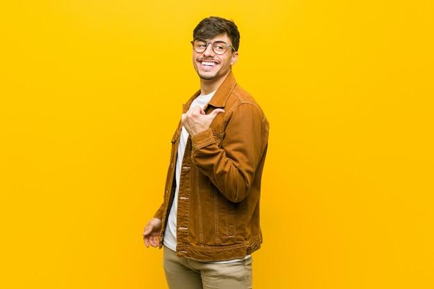 Il giovane uomo casuale ispanico indica con il pollice via, ridendo e spensierato.