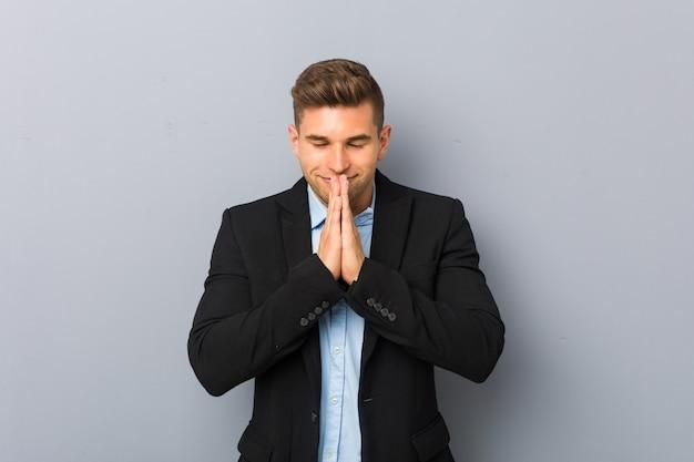 Il giovane uomo caucasico bello che si tiene per mano dentro prega vicino alla bocca, si sente sicuro.