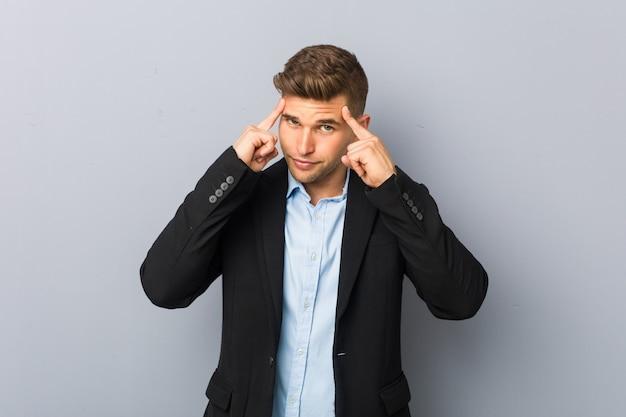Il giovane uomo caucasico bello si è concentrato su un compito, mantenendo l'indice che indica la testa.