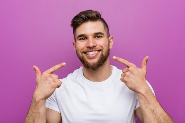 Il giovane uomo caucasico bello sorride, indicando le dita alla bocca.