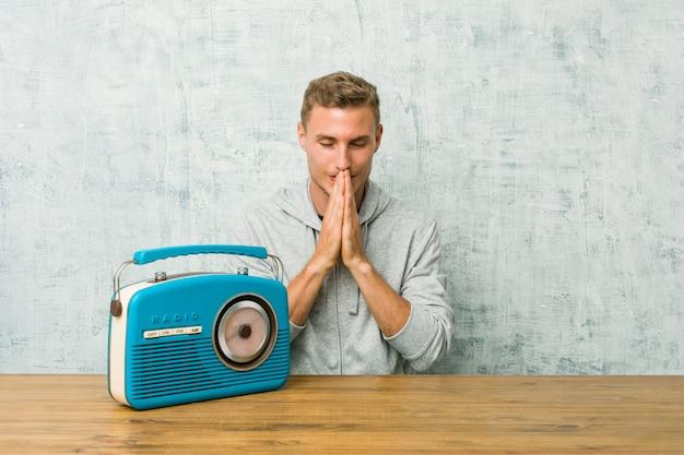 Il giovane uomo caucasico che ascolta la radio che si tiene per mano dentro prega vicino alla bocca, si sente sicuro.