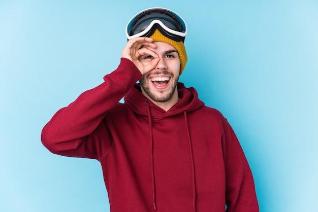 Il giovane uomo caucasico che indossa un abbigliamento da sci ha isolato eccitato mantenendo il gesto giusto sull'occhio.