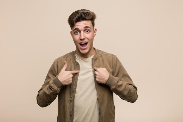 Il giovane uomo caucasico che indossa una giacca marrone sorpreso indicando se stesso, sorridendo ampiamente.