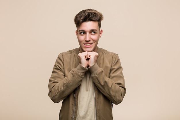 Il giovane uomo caucasico che indossa una giacca marrone tiene le mani sotto il mento, sta guardando felicemente da parte.