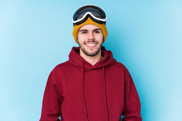 Il giovane uomo caucasico che indossa uno sci copre isolato felice, sorridente e allegro.