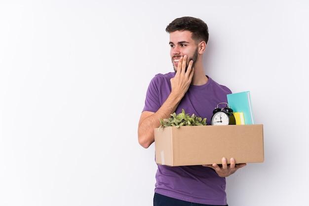 Il giovane uomo caucasico che muove una nuova casa sta dicendo una notizia di frenata calda segreta e sta guardando da parte