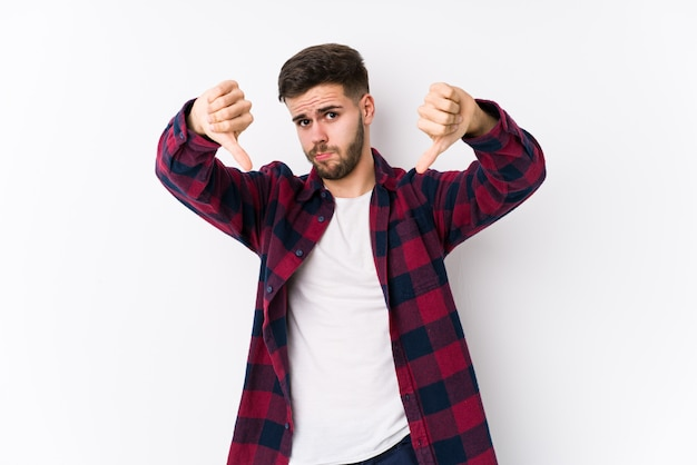 Il giovane uomo caucasico che posa in un fondo bianco ha isolato la mostra del pollice giù e l'espressione dell'antipatia.
