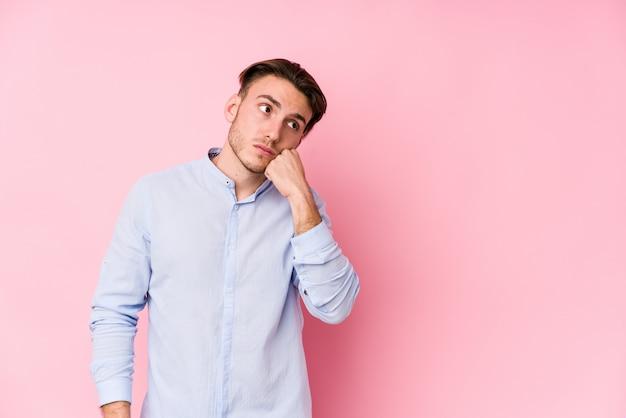 Il giovane uomo caucasico che posa in una parete rosa ha isolato chi si sente triste e pensieroso, esaminando lo spazio della copia.
