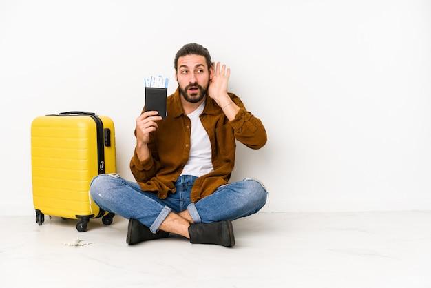 Il giovane uomo caucasico che si siede tenendo un passaporto e una valigia ha isolato provare ad ascoltare un gossip.