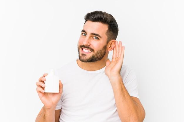 Il giovane uomo caucasico che tiene una bottiglia di vitamine ha isolato la prova di ascoltare un gossip.