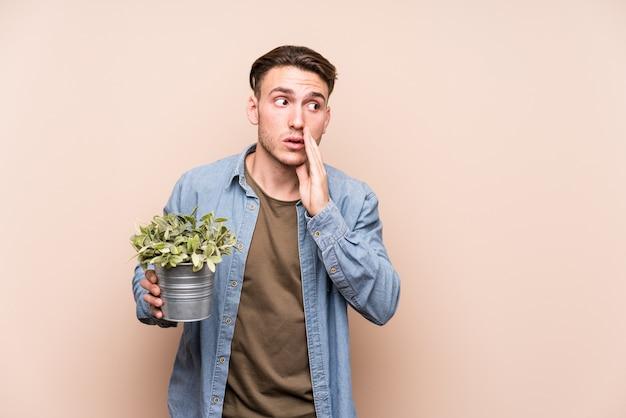 Il giovane uomo caucasico che tiene una pianta sta dicendo una notizia di frenata calda segreta e sta guardando da parte