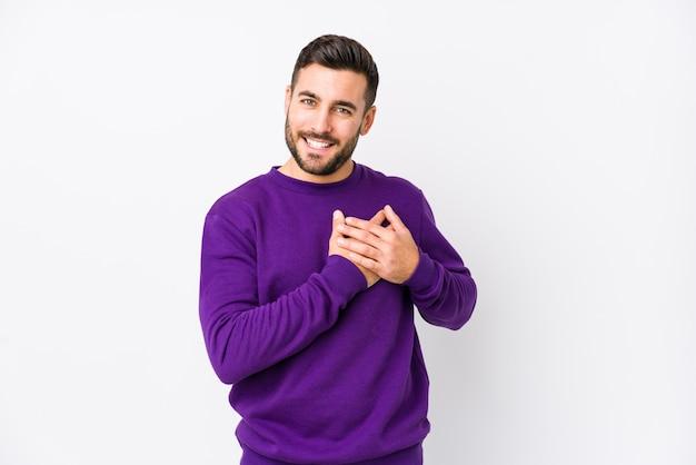 Il giovane uomo caucasico contro un muro bianco ha un'espressione amichevole, premendo il palmo sul petto