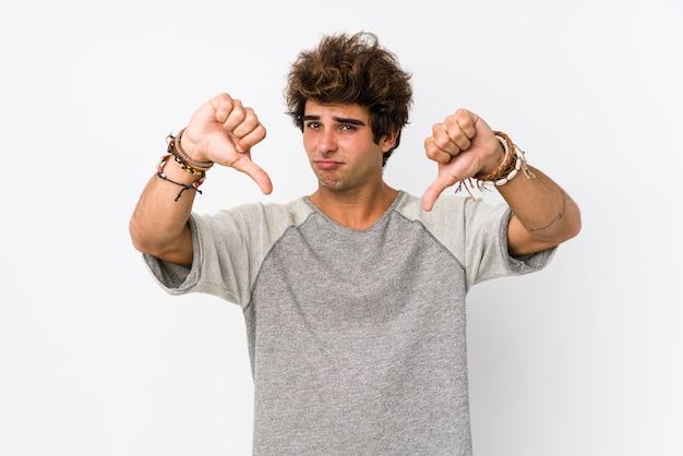 Il giovane uomo caucasico contro una parete bianca ha isolato la mostra del pollice giù e l'espressione dell'antipatia.