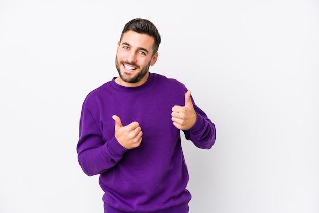Il giovane uomo caucasico contro una parete bianca ha isolato sollevando entrambi i pollici in su, sorridendo e sicuro.