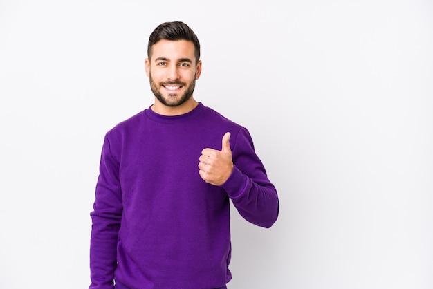 Il giovane uomo caucasico contro una parete bianca ha isolato sorridere e sollevare il pollice in su