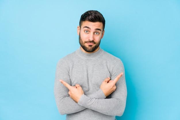 Il giovane uomo caucasico contro una parete blu ha isolato lateralmente i punti, sta provando a scegliere tra due opzioni.