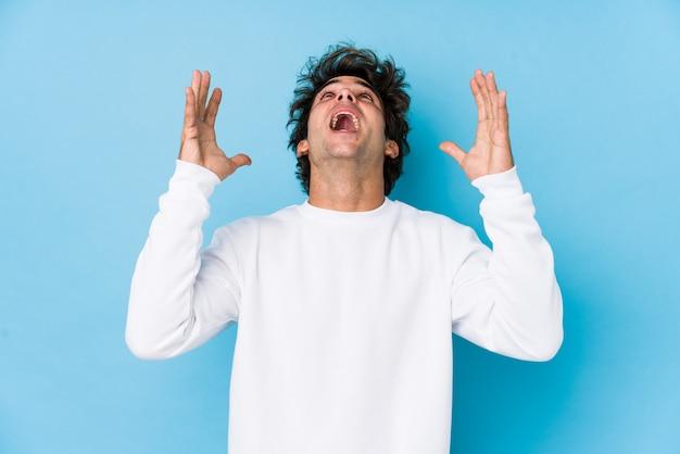 Il giovane uomo caucasico contro una parete blu ha isolato le grida al cielo, osservando in su, frustrato.