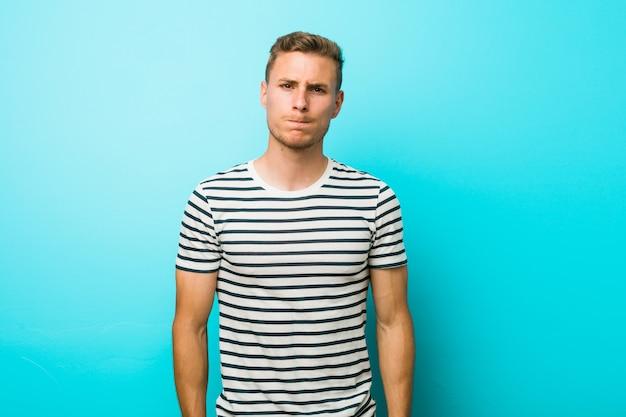 Il giovane uomo caucasico contro una parete blu soffia sulle guance, ha un'espressione stanca. concetto di espressione facciale.