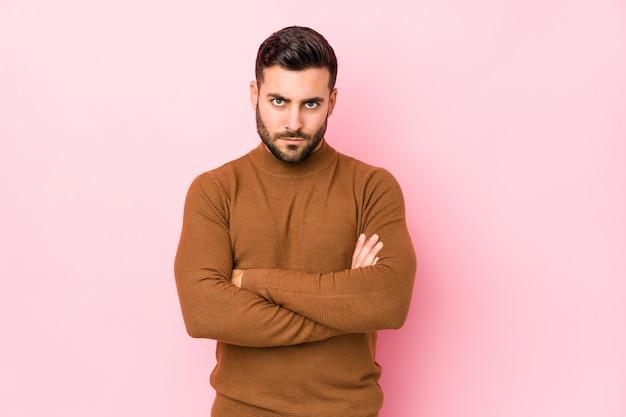 Il giovane uomo caucasico contro una parete rosa isolata fronte accigliata nel dispiacere, tiene le braccia conserte.
