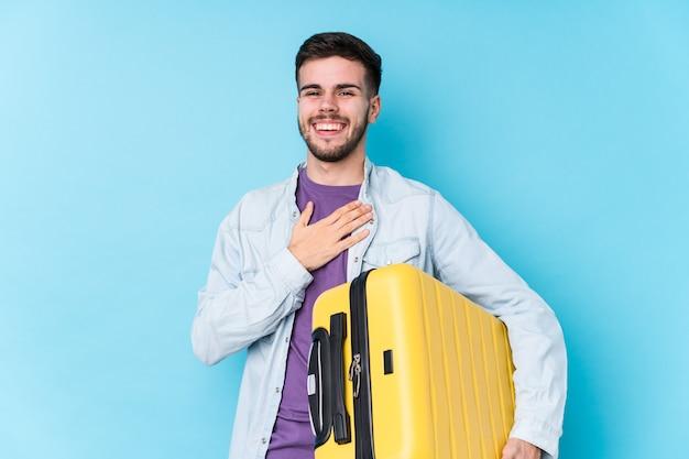 Il giovane uomo caucasico del viaggiatore che tiene una valigia isolata ride ad alta voce mantenendo la mano sul petto.