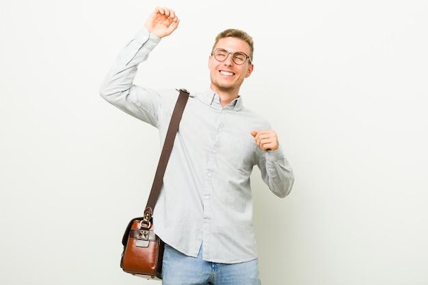 Il giovane uomo caucasico di affari che celebra un giorno speciale, salta e alza le braccia con energia.