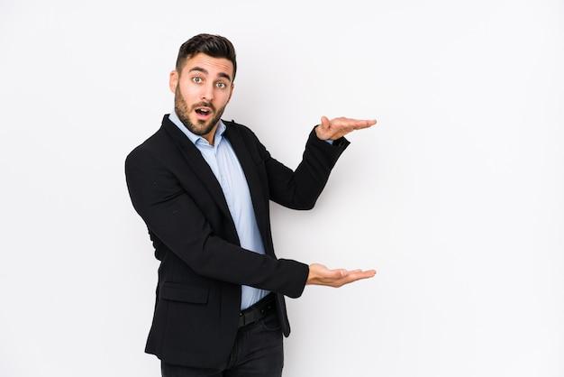 Il giovane uomo caucasico di affari contro una parete bianca ha isolato colpito e stupito tenendo uno spazio della copia fra le mani.
