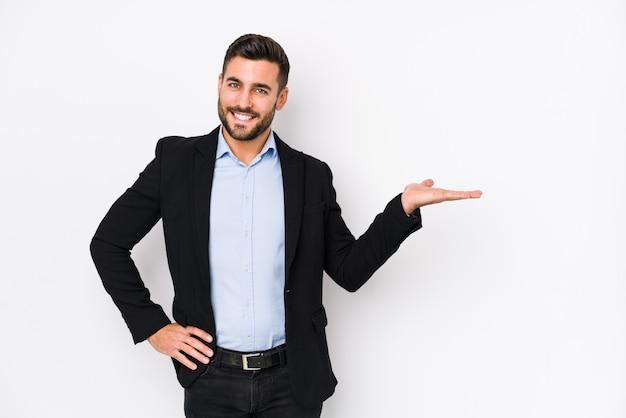 Il giovane uomo caucasico di affari contro una parete bianca ha isolato mostrando uno spazio della copia su una palma e tenendo un'altra mano sulla vita.