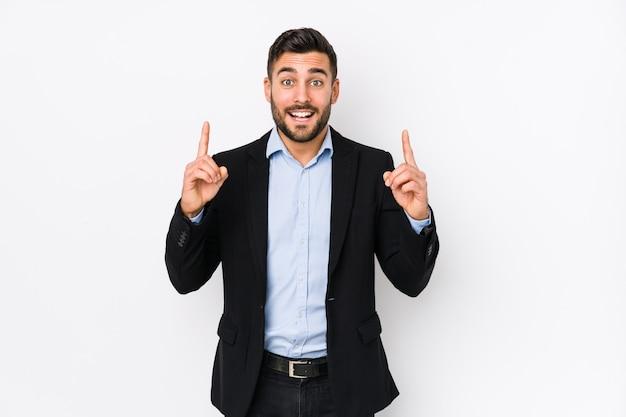 Il giovane uomo caucasico di affari contro una parete bianca isolata indica con entrambe le dita anteriori in su che mostrano uno spazio.