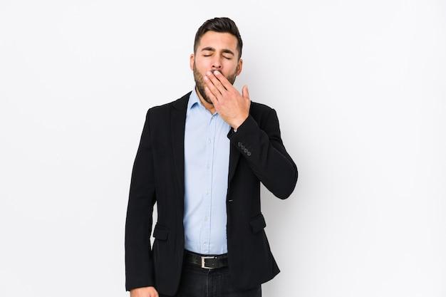 Il giovane uomo caucasico di affari contro una priorità bassa bianca ha isolato lo sbadiglio mostrando un gesto stanco che copre la bocca di mano.