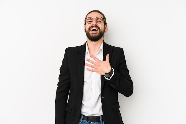 Il giovane uomo caucasico di affari isolato su bianco ride ad alta voce tenendo la mano sul petto.