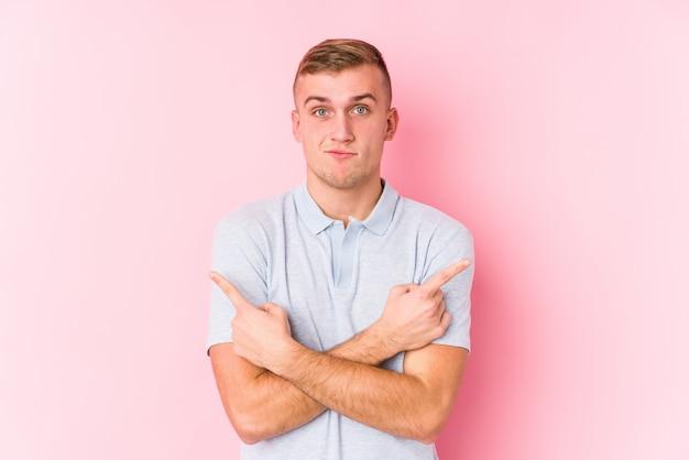 Il giovane uomo caucasico indica lateralmente, sta provando a scegliere tra due opzioni.
