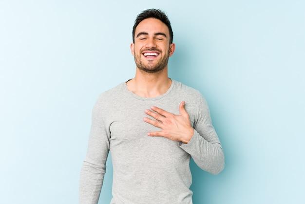 Il giovane uomo caucasico isolato sull'azzurro ride ad alta voce tenendo la mano sul petto.