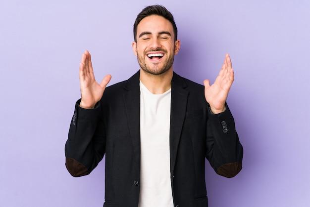 Il giovane uomo caucasico isolato sulla porpora ride ad alta voce tenendo la mano sul petto.