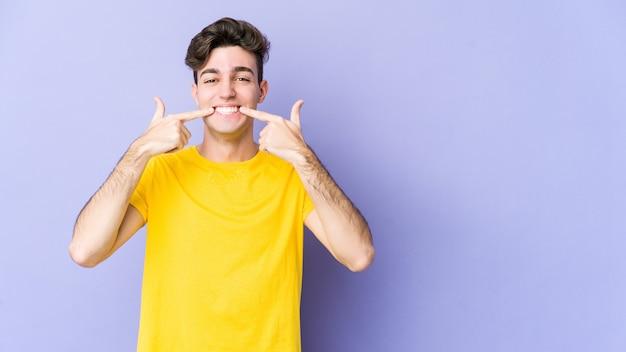 Il giovane uomo caucasico sorride, indicando le dita alla bocca.