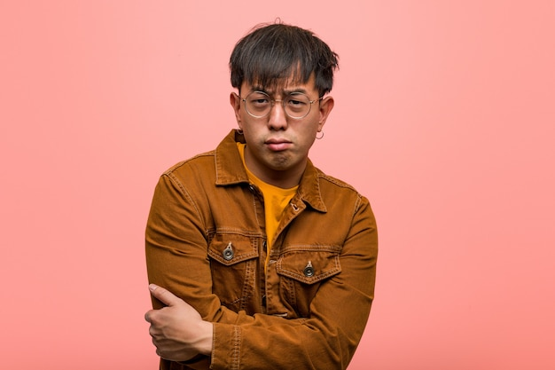 Il giovane uomo cinese che indossa un incrocio del rivestimento arma rilassato