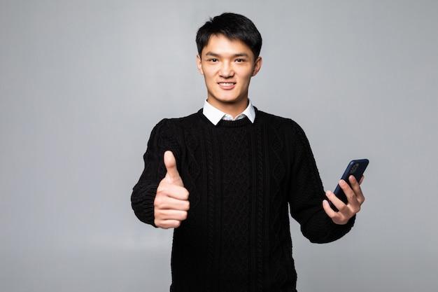 Il giovane uomo cinese che parla sullo smartphone che sta soddisfatto del grande sorriso che fa il segno giusto, sfoglia su con le dita, eccellente firma sopra la parete bianca isolata