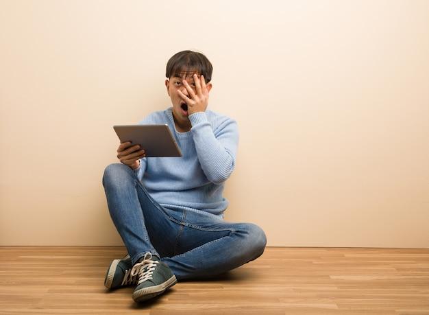 Il giovane uomo cinese che si siede facendo uso della sua compressa si sente preoccupato e sca
