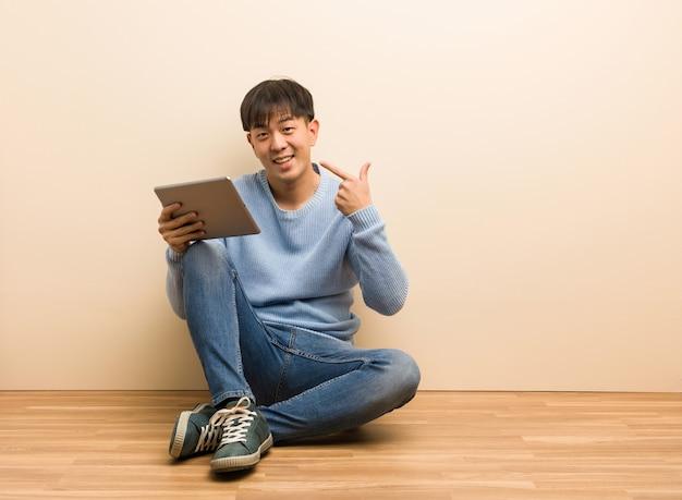 Il giovane uomo cinese che si siede facendo uso della sua compressa sorride, indicando la bocca