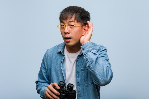 Il giovane uomo cinese che tiene un binocolo prova ad ascoltare un gossip
